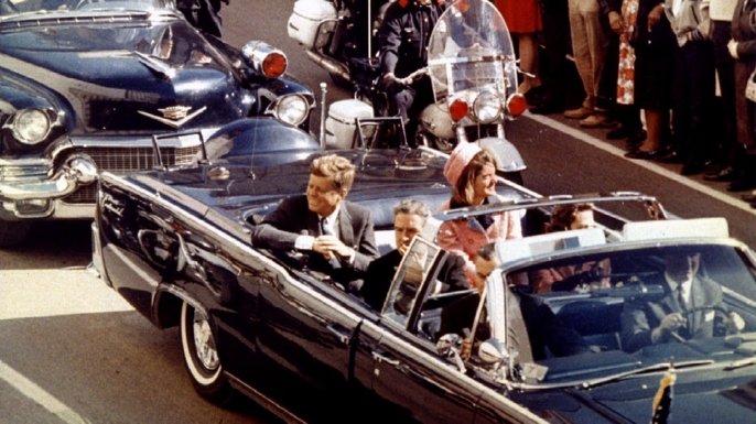 John and Jacqueline Kennedy ride through Dallas, Texas, on November 22, 1963. (Credit: Getty Images)