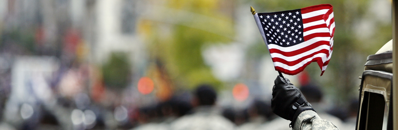 U.S. Armed Officer Waves American Flag on Veteran's Day