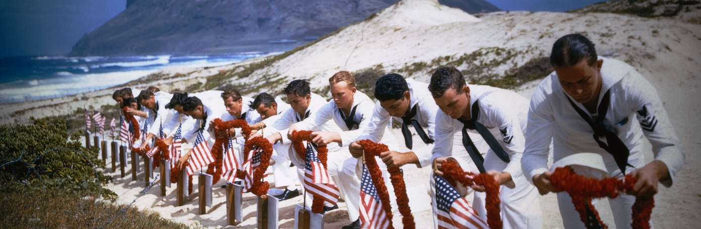 Navy members put leis on the graves of their fallen comrades on the beach in Hawaii where Pearl Harbor was attacked