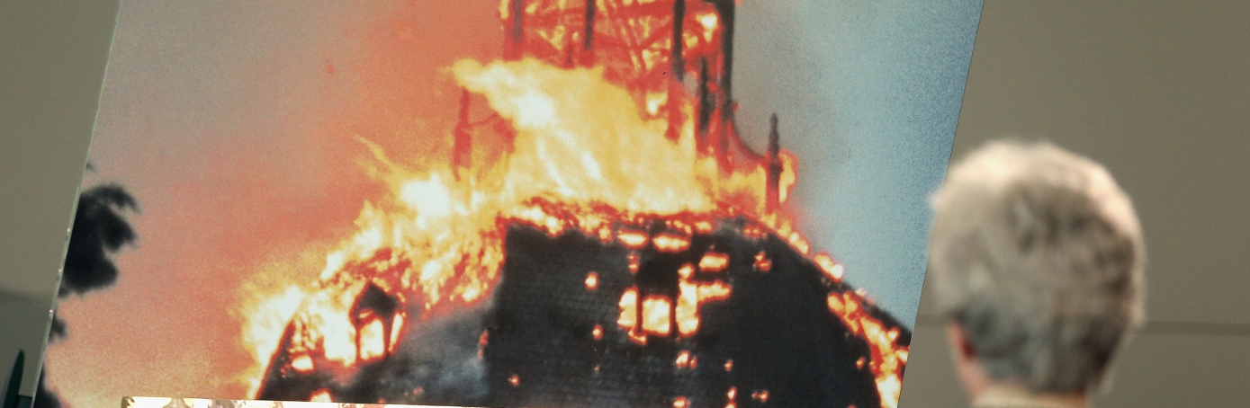 A visitor looks on a photo of a burning synagogue.