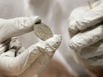 "Hatchfield holding the 1652 ""Pine Tree Shilling"" found in the capsule (Credit: Bostom Museum of Fine Arts)"