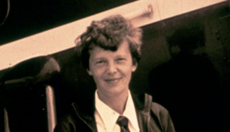 Photo of pilot Amelia Earhart standing by her plane. (Credit: Getty Images)