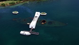 Aerial view of the USS Arizona Memorial at Pearl Harbor, Hawaii. The ship's wreckage has been leaking oil, visible in the upper left, for nearly 70 years.