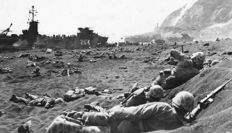 U.S. Marines take cover on the beach at Iwo Jima