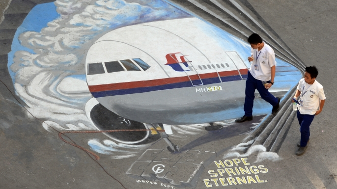 Students walk past a mural dedicated to Malaysia Airlines Flight 370