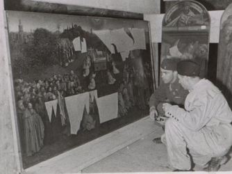 Members of the Monuments Men group examines part of the recovered Ghent Altarpiece.
