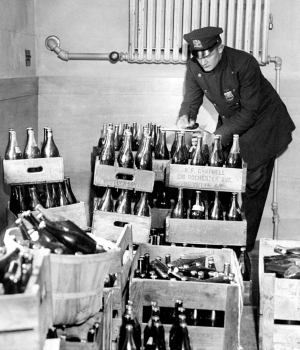 New York City police officer examines confiscated alcohol. (Credit: Art Edger/NY Daily News/Getty Images)