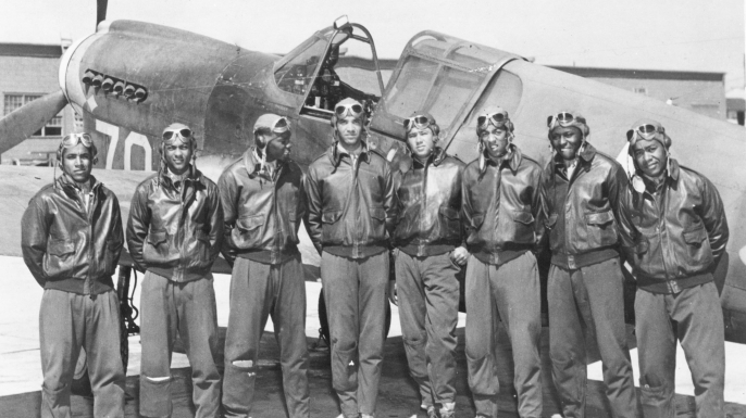 Eight Tuskegee airmen pose in front of a P-40 fighter in 1942 or 1943.