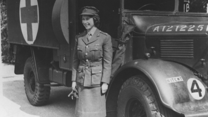 Elizabeth wears an officer's uniform and stands beside an Auxiliary Territorial Service first aid truck during World War II.