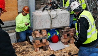 Officials work to remove the time capsule from the cornerstone of the Massachusetts State House.