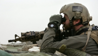 A Navy SEAL observes enemy movements.