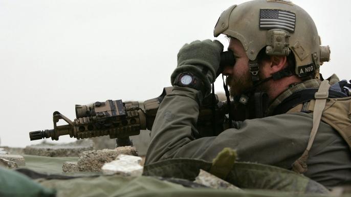 A Navy SEAL observes enemy movements.