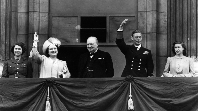 British Prime Minister Winston Churchill and the British royal family waving from the balcony of Buckingham Palace during V-E Day celebrations in London. (Credit: Reg Speller/Getty Images)