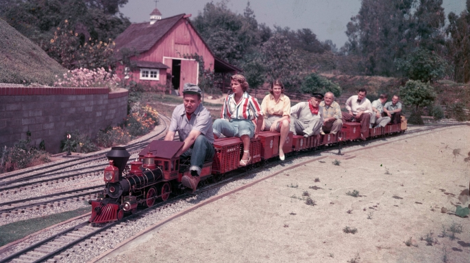 Disney drives a miniature railroad filled with passengers at his California home. (Credit: Gene Lester/Archive Photos/Getty Images)