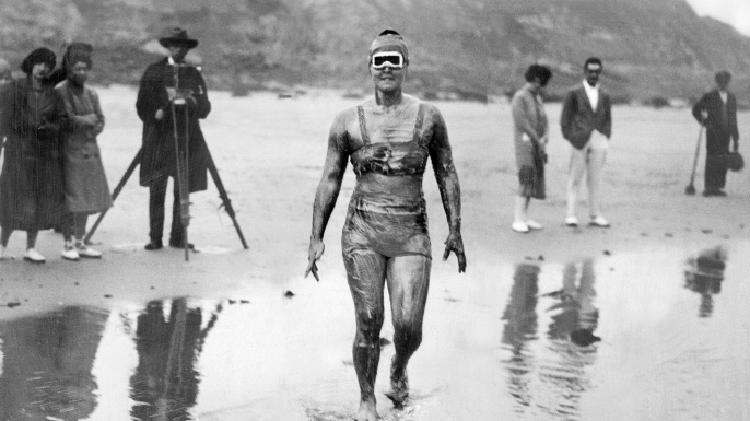 Coated in grease, Gertrude Ederle wades into the water on August 6, 1926, beginning her successful attempt to swim the English Channel.