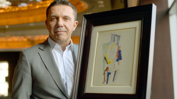 "Olivier Picasso, Pablo Picasso's grandson, poses with a painting entitled L'Homme au Gibus or ""Man with Opera Hat,"" which will be raffled off on December 18, 2013"