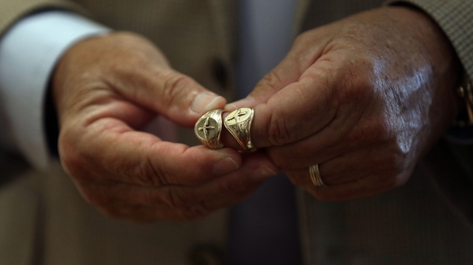 David Cox, Jr holds a replica ring (right) and the original (left) that belonged to his father, U.S. Army Air Corps member David Cox.