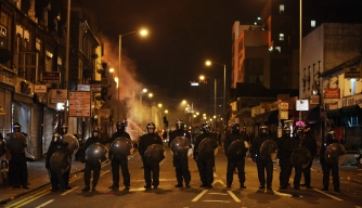 LONDON, ENGLAND - AUGUST 09:  Police officers patrol the streets as a large fire engulfs shops and residential properties in Croydon on August 9, 2011 in London, England. Sporadic looting and clashes with police continue for a third day in parts of the capital after the killing of the 29-year-old father of four Mark Duggan by armed police in an attempted arrest on August 4.  (Photo by Dan Kitwood/Getty Images)