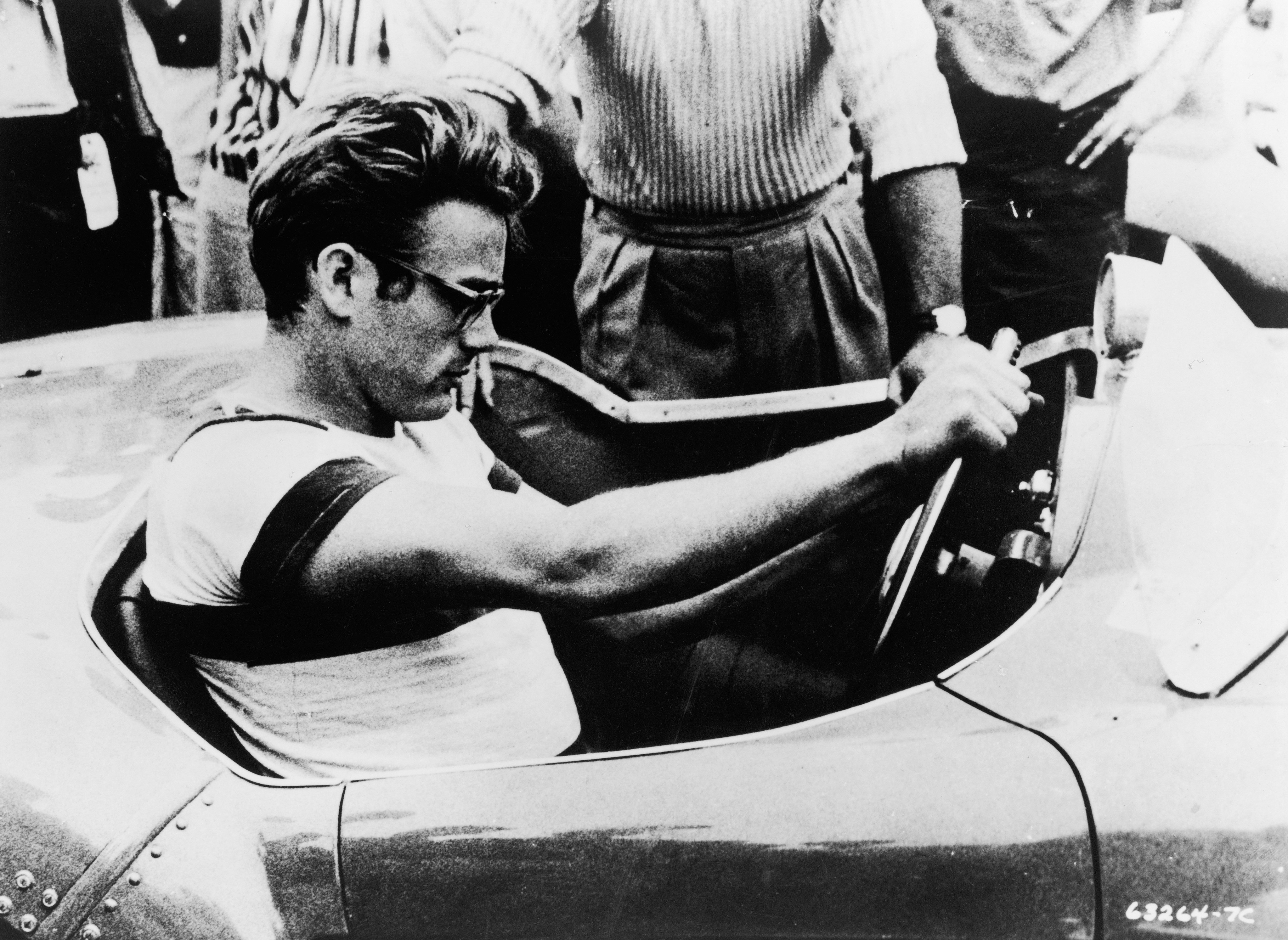 james dean sits behind the wheel of a sports car in a still from the