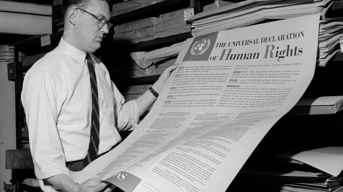 A man looks at one of the first documents published by the United Nations, The Universal Declaration of Human Rights.  (Credit: Three Lions/Getty Images)