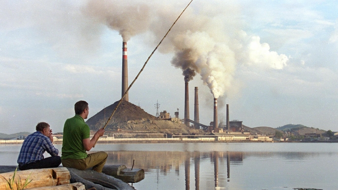 Two local men try to catch some fish in a lake next to Karabash copper smelting plant. (Credit Alexander Nemenov/Getty Images)