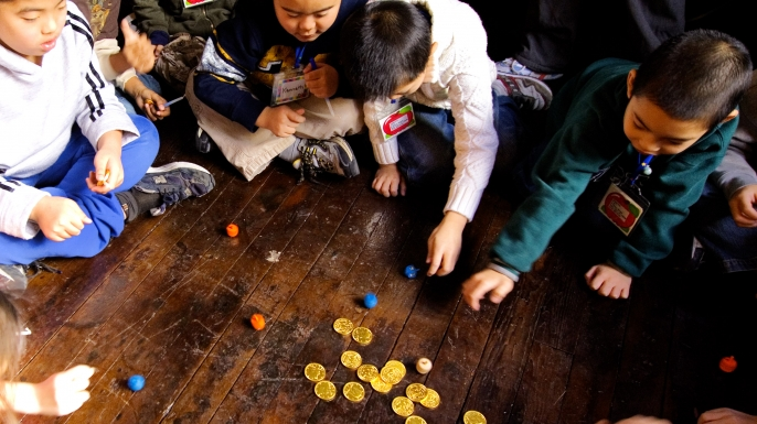Second grade students play with dreidels and chocolate gold coins.  (Credit: Stephen Chernin/Getty Images)