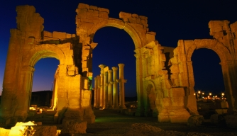 Floodlit monumental arch marking the entrance to Palmyra. (Credit: Mark Daffey / Getty Images)