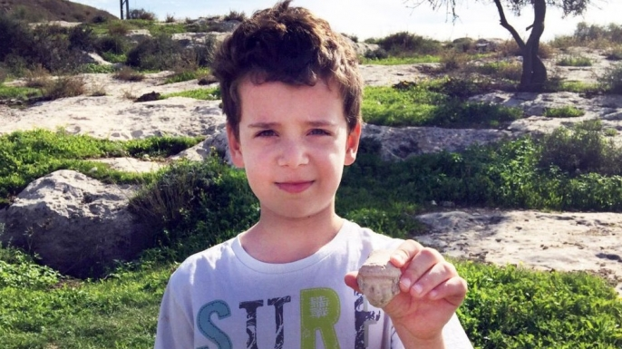Itai with the head of the statuette he found on Tel Beit Shemesh. (Credit: Courtesy Israel Antiquities Authority/the Ministry of Foreign Affairs)