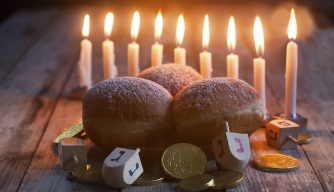 Menorah, donuts, chockolate coins and wooden dreidels. (Credit: Karaidel/http://www.istockphoto.com)