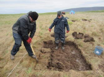 Chase Childs (L) & Sarah Parcak (R) removing upper grass layer. (Credit: Greg Mumford)