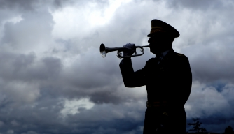 Silhouette of a man playing taps on his bugle. (Credit: gjohnstonphoto/istockphoto.com)