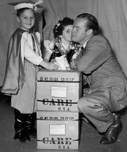 Bob Hope in Poland with children dressed in European costumes. (Credit: CARE)