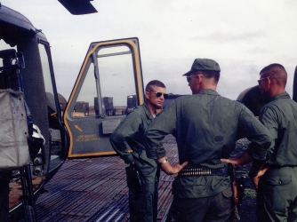 "U.S. Army Maj. Charles Kettles (left), standing beside his heavily damaged ""Huey"" helicopter on return from the May 15, 1967 emergency extraction rescue operation. (Credit: Retired U.S. Army Lt. Col. Charles Kettles)"