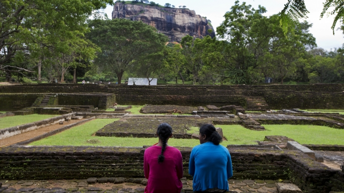 Visitors sit in front of the 'Lion Rock' in the gardens of the Ancient City of Sigiriya. (Credit: Kuni Takahashi/Bloomberg/Getty Images)