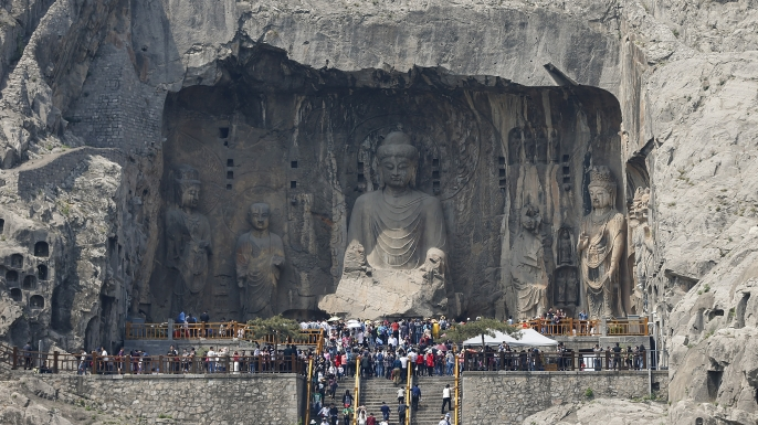 Tourists view Buddhist sculptures at Longmen Grottoes on April 10, 2016 in the outskirts of Luoyang of Henan Province, China.  (Credit: Lintao Zhang/Getty Images)