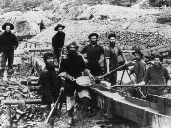 Miners display a large gold nugget during the Klondike Gold Rush.