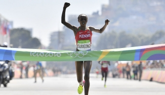 Kenya's Jemima Jelagat Sumgong raises her arms in victory as she crosses the finish line of the Women's Marathon during the athletics event at the Rio 2016 Olympic Games. (Credit: Fabrice COFFRINI-Pool / Getty Images)