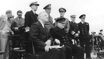 President Franklin D. Roosevelt (left) and Prime Minister Winston Churchill during Church services on the after deck of HMS Prince of Wales, during the Atlantic Charter Conference. (Credit: U.S. Navy)