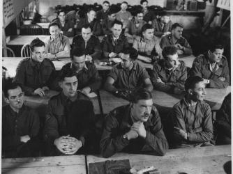 View of the audience, seated in rows and listening during a demolition class, in England, 1944. Office of Strategic Services. (Credit: Public Domain)
