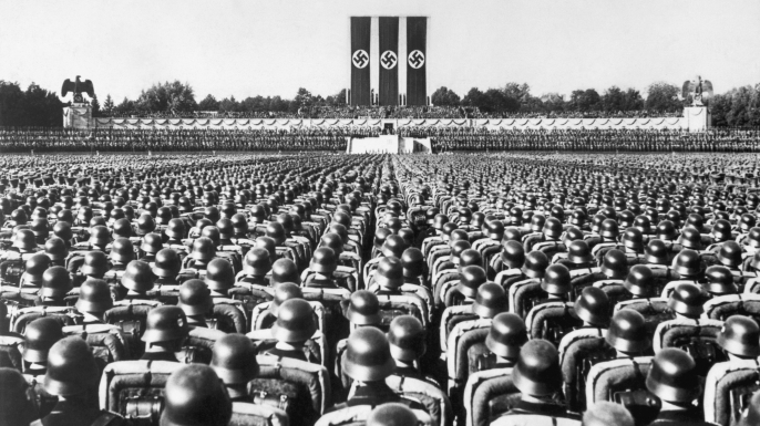 A huge crowd of soldiers stands at attention beneath the reviewing stand at a 1936 Nazi rally in Nuremberg, Germany.