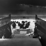 06 Jun 1944, Normandy, France --- On D-Day, June 6, 1944, a landing craft just vacated by invasion troops points towards a fortified beach on the Normandy Coast. American soldiers wade to shore fighting heavy machine gun fire. --- Image by © CORBIS