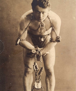 Houdini in chains during a stunt.