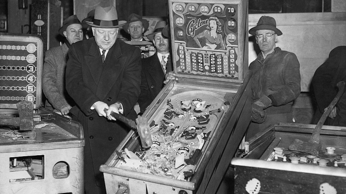 New York City Police Commissioner William P. O'Brien smashes illegal pinball machines in a warehouse in the Greenpoint section of Brooklyn. (Credit: Bettmann/Getty Images)