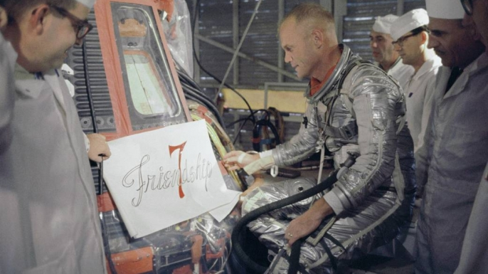 "Glenn inspecting the artwork design for ""Friendship 7."" (Credit: NASA)"
