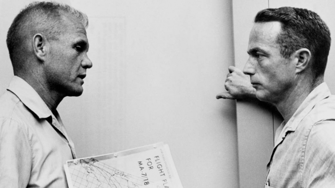 John Glenn and Scott Carpenter reviewing the flight plan for the Mercury-Atlas 7 mission at Cape Canaveral, Florida. (Credit: NASA)
