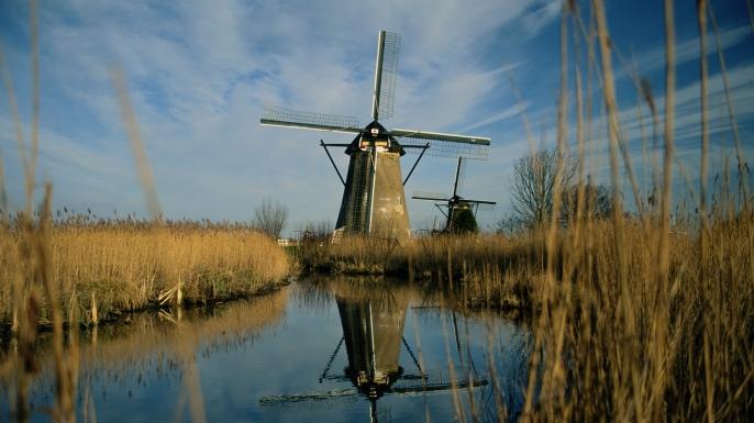 Lek River in Netherlands Windmills in wheat field. (Credit: Jochem D Wijnands/Getty Images)