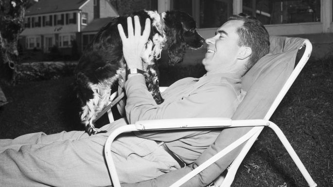 "GOP Vice Presidential candidate Sen. Richard Nixon of California relaxes at home in Washington with the family pet, a Cocker Spaniel named ""Checkers."" (Credit: Bettmann/Getty Images)"