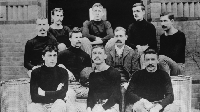 The first basketball team, consisting of nine players and their coach on the steps of the Springfield College Gymnasium in 1891 are shown. Dr. Naismith is in civilian clothes. (Credit: Bettmann/Getty Images)