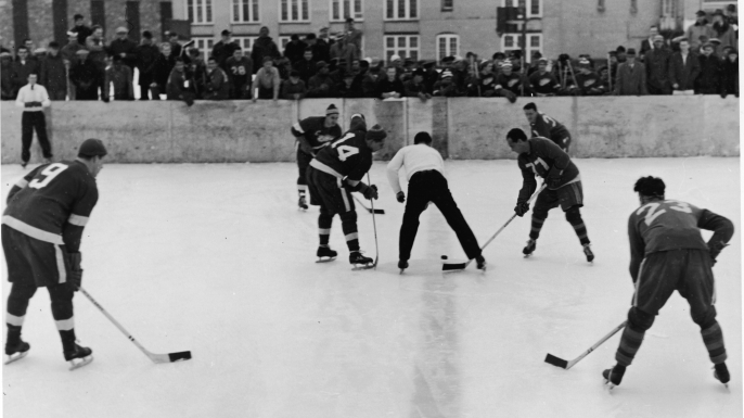 Gordie Howe, Dutch Reibel and Ted Lindsay of the Detroit Red Wings line up for the faceoff during an outdoor game against the Marquette Prison Pirates on February 2, 1954 at the Marquette prison in Marquette, Michigan. (Credit: Bruce Bennett Studios/Getty Images)