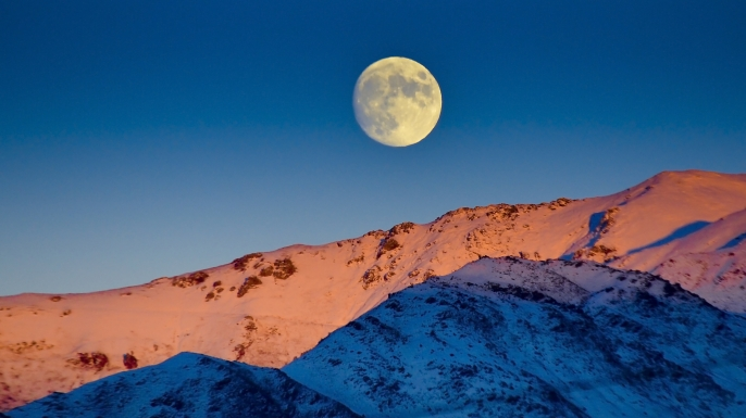 Moon rises over snow capped mountains at twilight, Winter Solstice. (Credit: 1255k / www.istockphoto.com)